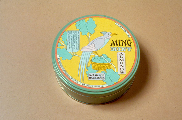 Mint Almond tin; cover is a blue bird perched atop a clutch of eggs in a tree against a yellow sky