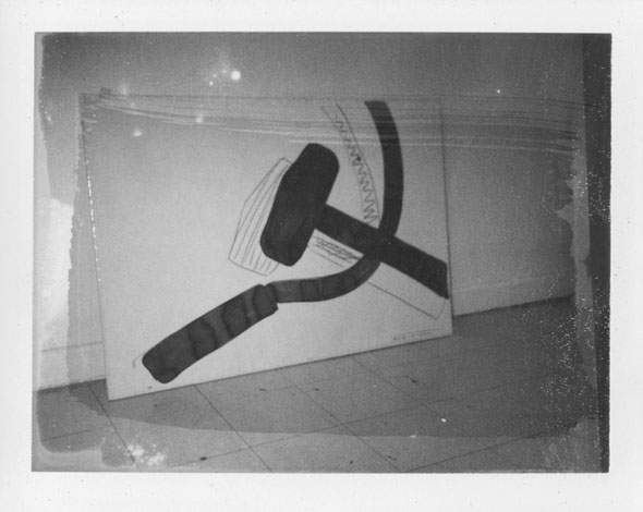 A photo of a a huge canvas of a different version of the drawing of the mallet and the sickle. The drawing is much similar to the previous ones but is far less detailed. The photo is as a thick smear going across the photo causing that area to be slightly darker.