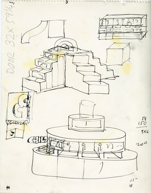 A rough pen sketch on a stained white paper. The sketch is planing layout, some of the drawings is hard to make out what it is. There us also dimension, numbers, random shapes on the sides of the paper. On the top right is a small cubby design. Below is big design of four set staircase going up to the same platform that has a rainbow on top. On the bottom is a design for what looks like a front desk. It has a cylindrical pyramid shape.