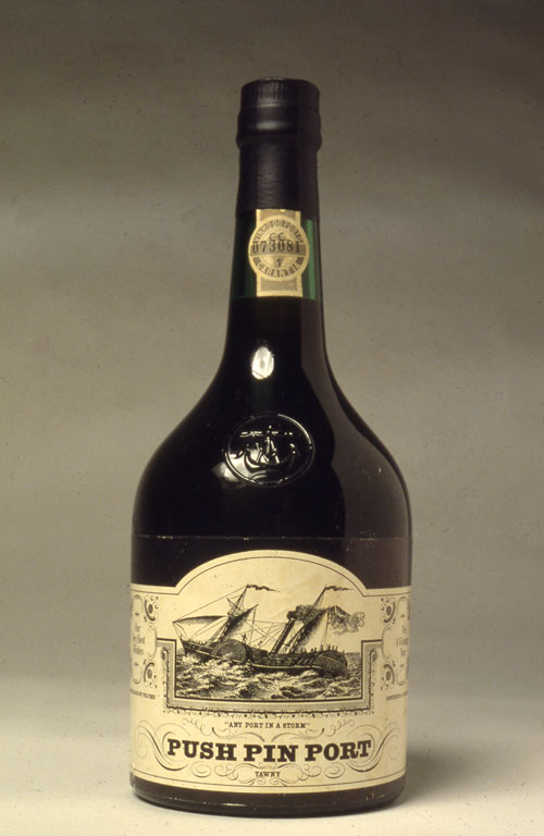 "A photo of a short and stout alcohol bottle.The label for the bottle in a black and white illustration of a big wooden boat sailing on the sea. Below is ""Any Port n a Storm"" in very small think text and underneath is ""Push Pin Port"" In thick bold black text. The rest of the label has small fancy details."