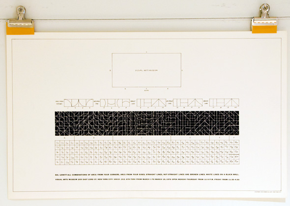 Print, held to board by clips, of a poster with black and white grid blocks on it
