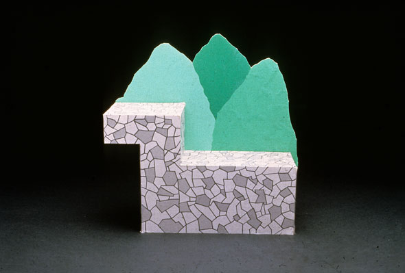 Photograph of a lounge seat on two levels, resembling rock, with stylized green trees as back support