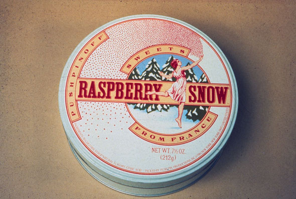 """Raspberry Snow"" candy tin; cover is illustration of a woman in a white dress dancing in a snowy forest, throwing red dots behind her"