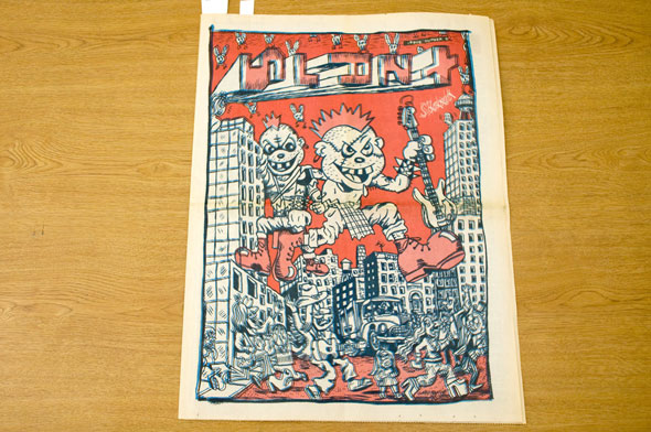 "A front or back cover of a news paper. Two punk rock, grunge looking teens are giants. They step over buildings with people running away from them. The illustration has navy blue outlines and white and dull red shading. In the red sky the title of the News Paper, ""Slant"" is written is a way where every over letter is turned 90 degrees."