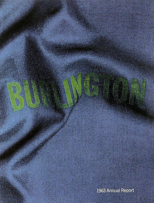 "A photo of a dark blue denim fabric. ""Burlington"" in sewn into the fabric with bright green bold lettering. The fabric has a few folds that cause the lettering to curve. On the bottom of the photo in white text ""1963 Annual Report""."