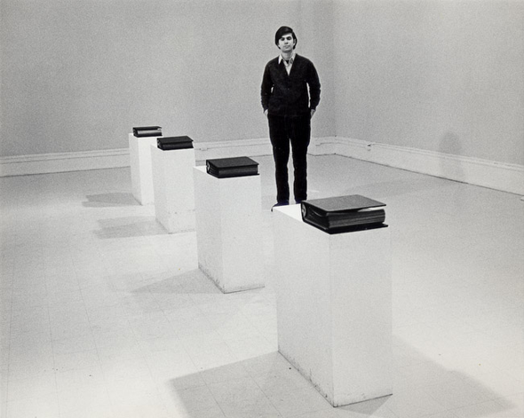 Black and white photo of a man standing in an art gallery; there are 4 binders mounted on pedestals