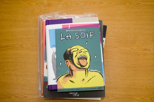 Photo of a Stack of books on a table; top reads La Soif and shows a yellow man sticking his tongue out to catch white droplets against a teal background