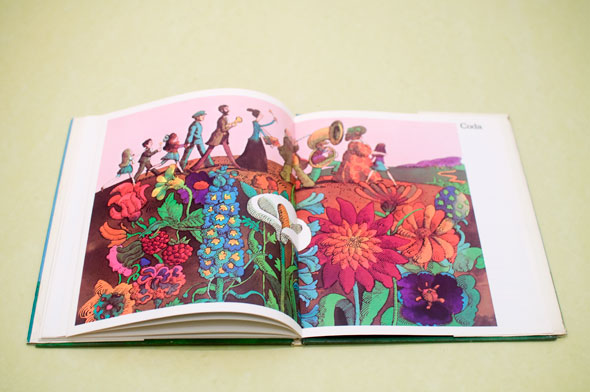 A photo of an opened book. The book is opened to a page of an illustration of line of musicians walking on a field of flowers.  There are 10 people on the line of musicians, some carry an instrument or is holding a kid's hand. The flowers are all different types of flowers, their colors are saturated and colorful.