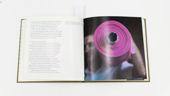 An opened book of a photo focused on a pink-purple roll of synthetic fabric, carried by a man's shoulder.