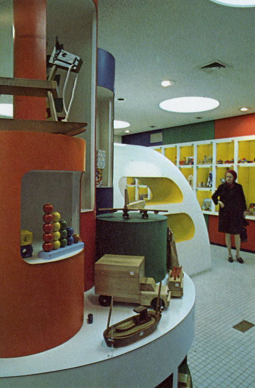 A photo of the back of the location. A geometrical colorful set of large and small cylinders with holes served as shelfs. The cylinder shelfs are on top of a white circular table that is covered in toys. The floor is tiny white swore tiles. The lighting on the ceiling are big white circular lights. And the wall of the cubbies is minimalistic yet colorful. The wall is a rainbow stripped design and the white cubbies has a bright yellow inside the cubbies.