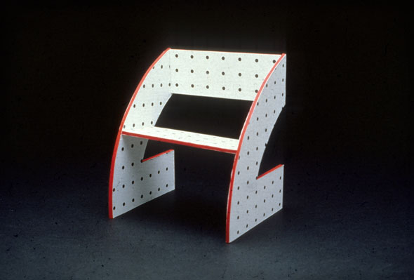 Photograph of a red-edged chair in an odd geometric shape, with a black and white dot pattern