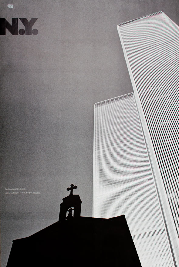 Ground view black and white photograph of two buildings; a shadowed church steeple is visible in foreground