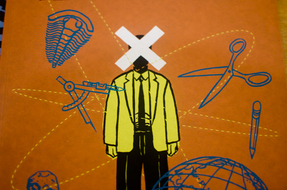 Simple drawing of a person in black pants and a yellow jacket with a large white X over their face, surrounded by a fossil, compass, pencil, globe, scissors.