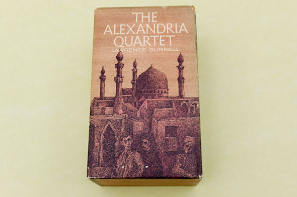 "A photo of the book, ""The Alexandria Quartet"". The cover has the title printed on the top in thin white text. The background is a dusty brown sky. Below is a town of small houses and building in the middle adorned with detailed decorations. In the foreground, are 3 people who's form are lost with the dark sketches of the houses."
