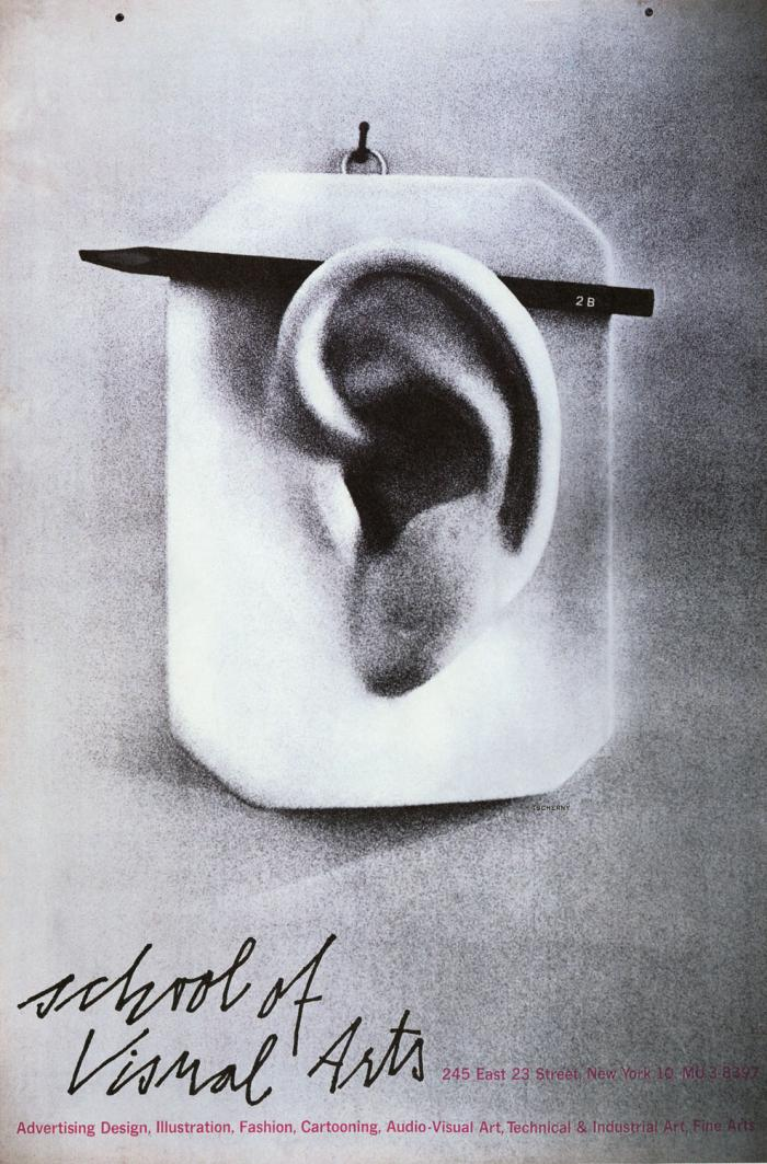 Black and white photograph of a model of a human ear with a real pencil tucked behind it.